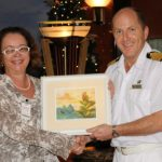Catherine Cooper of Cox & Co. Ltd. presenting to the captain of the RMS Queen Mary 2 on its first visit to St. Lucia, December 2010